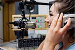 Smiling radio host speaking through a microphone Stock Photo - Royalty-Free, Artist: 4774344sean                   , Code: 400-05672203