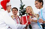 Image of cheering associates taking gifts from ceo in Santa cap at corporate party Stock Photo - Royalty-Free, Artist: pressmaster                   , Code: 400-05672543