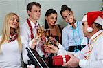 Image of cheering associates congratulating ceo in Santa cap at corporate party Stock Photo - Royalty-Free, Artist: pressmaster                   , Code: 400-05672548