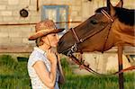 Woman in hat kissing a brown horse Stock Photo - Royalty-Free, Artist: pavelshlykov                  , Code: 400-05673589