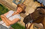 Woman in hat staying above brown horse Stock Photo - Royalty-Free, Artist: pavelshlykov                  , Code: 400-05673590
