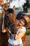 Woman in hat embrace brown horse Stock Photo - Royalty-Free, Artist: pavelshlykov                  , Code: 400-05673595