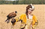 The woman in a beautiful old style dress with falcon has a rest before hunting in yellow field. Stock Photo - Royalty-Free, Artist: pavelshlykov                  , Code: 400-05673725