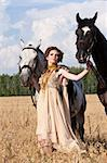 The woman in a beautiful old style dress with two horses in yellow field. Stock Photo - Royalty-Free, Artist: pavelshlykov                  , Code: 400-05673785