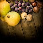 Nature background made of autumn fruit and beautiful sunlight in the back. Grapes, chestnut, vine leaf, walnuts, quince and apples. Stock Photo - Royalty-Free, Artist: mythja                        , Code: 400-05674125