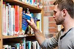 Male student picking a book in a library Stock Photo - Royalty-Free, Artist: 4774344sean                   , Code: 400-05678156