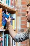 Portrait of a male student picking a book in a library Stock Photo - Royalty-Free, Artist: 4774344sean                   , Code: 400-05678157