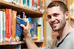 Smiling male student picking a book in a library Stock Photo - Royalty-Free, Artist: 4774344sean                   , Code: 400-05678159
