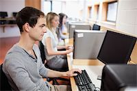 Smiling male student posing with a computer in an IT room Stock Photo - Royalty-Freenull, Code: 400-05684121
