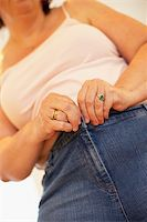 Overweight Woman Trying To Fasten Trousers Stock Photo - Royalty-Freenull, Code: 400-05686625