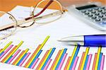 Colorful business chart, blue pen calculator and eyeglasses