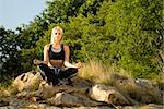 Pretty woman meditating on rock lotus hands with gold light reflector Stock Photo - Royalty-Free, Artist: alistaircotton                , Code: 400-05694395