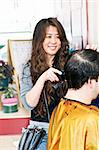 Happy hairdresser cutting hair in her salon Stock Photo - Royalty-Free, Artist: Elenathewise                  , Code: 400-05695752