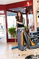 Smiling hairstylist sweeping hair clippings on floor in her salon Stock Photo - Royalty-Freenull, Code: 400-05695755
