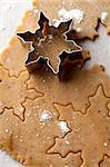 Making gingerbread cookies for Christmas. Gingerbread dough with star shapes and a cutter.