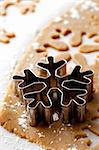 Making gingerbread cookies for Christmas. Gingerbread dough with snowflake shapes.