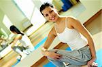 Portrait of happy sportive girl sitting on the floor of gym during training Stock Photo - Royalty-Free, Artist: pressmaster                   , Code: 400-05712050