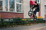 Biker doing icepick grind trick on low, black rail