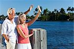 Happy senior man and woman couple together outside in sunshine waving by the sea on a jetty or pier Stock Photo - Royalty-Free, Artist: darrenbaker                   , Code: 400-05721409