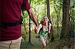 young man and woman walking in woods, with man helping his girlfriend. Horizontal shape, three quarter length Stock Photo - Royalty-Free, Artist: diego_cervo                   , Code: 400-05721653