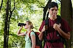 young people trekking among trees and looking at birds with binoculars. Horizontal shape, side view, waist up Stock Photo - Royalty-Free, Artist: diego_cervo                   , Code: 400-05721654