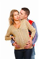 Young husband kissing his pregnant wife  on white background    Stock Photo - Royalty-Freenull, Code: 400-05730247
