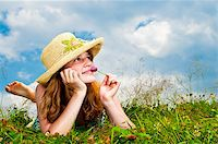 Young teenage girl laying in summer meadow resting chin on hand smelling flower Stock Photo - Royalty-Freenull, Code: 400-05731720