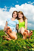 Two young teenage girl friends sitting barefoot on summer meadow Stock Photo - Royalty-Freenull, Code: 400-05731721