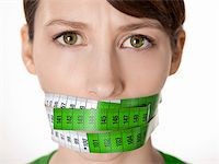 Portrait of a young  woman with a green measuring tape covering the mouth Stock Photo - Royalty-Freenull, Code: 400-05734428