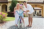 A young family with girl child riding a bicycle and her happy parents giving encouragement Stock Photo - Royalty-Free, Artist: darrenbaker                   , Code: 400-05735848