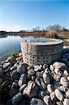 A perforated concrete pipe forms part of a stormwater management system in a suburban pond. Stock Photo - Royalty-Free, Artist: brianguest                    , Code: 400-05739871