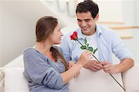 Man offering a rose to his girlfriend in their living room Stock Photo - Royalty-Freenull, Code: 400-05739986