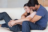 Man kissing his girlfriend in the neck in their living room Stock Photo - Royalty-Freenull, Code: 400-05742615