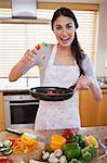 Portrait of a happy woman preparing a dish in her kitchen
