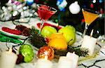Image of holiday table with cocktails, fruits, burning candles and decorations on it