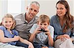 Charming family playing video games in a living room Stock Photo - Royalty-Free, Artist: 4774344sean                   , Code: 400-05749609