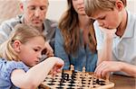 Focused siblings playing chess in front of their parents in a living room
