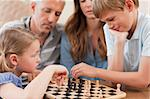 Close up of siblings playing chess in front of their parents in a living room Stock Photo - Royalty-Free, Artist: 4774344sean                   , Code: 400-05749617