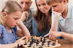 Close up of children playing chess in front of their parents in a living room