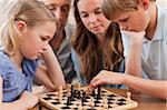 Close up of serious children playing chess in front of their parents in a living room Stock Photo - Royalty-Free, Artist: 4774344sean                   , Code: 400-05749619