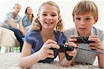 Playful siblings playing video games with their parents on the background in a living room Stock Photo - Royalty-Free, Artist: 4774344sean                   , Code: 400-05749633