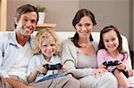 Smiling family playing video games together in a living room Stock Photo - Royalty-Free, Artist: 4774344sean                   , Code: 400-05749665