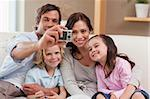 Father taking a picture of his family in the living room Stock Photo - Royalty-Free, Artist: 4774344sean                   , Code: 400-05749677
