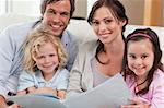 Close up of a family looking at a photo album in a living room Stock Photo - Royalty-Free, Artist: 4774344sean                   , Code: 400-05749682