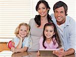 Smiling family using a tablet computer together in a kitchen Stock Photo - Royalty-Free, Artist: 4774344sean                   , Code: 400-05749719