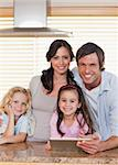 Portrait of a smiling family using a tablet computer together in a kitchen Stock Photo - Royalty-Free, Artist: 4774344sean                   , Code: 400-05749720