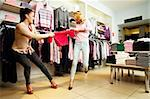 Image of two greedy girls fighting for red tanktop in department store Stock Photo - Royalty-Free, Artist: pressmaster                   , Code: 400-05750985