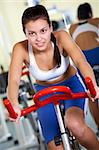 Portrait of young female training on simulator in gym Stock Photo - Royalty-Free, Artist: pressmaster                   , Code: 400-05750995