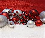 Christmas decorations nestled in snow on a glittery red background Stock Photo - Royalty-Free, Artist: kirstypargeter                , Code: 400-05751092