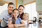 Smiling family standing together behind the kitchen counter Stock Photo - Royalty-Free, Artist: 4774344sean                   , Code: 400-05751191